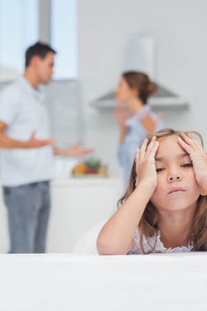 Girl annoyed while listening to parents quarreling in the kitchen photo