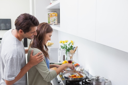 vegetables young couple: Man looking at his wife cooking in kitchen