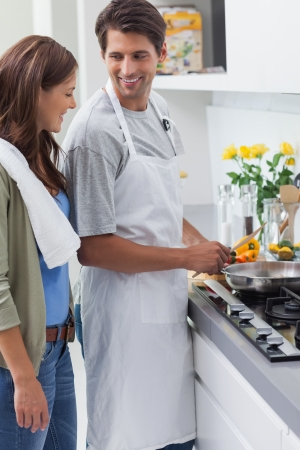 Man wearing apron and cooking in the kitchen photo