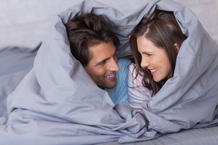 Cheerful couple having fun wrapped in their duvet at home Stock Photo
