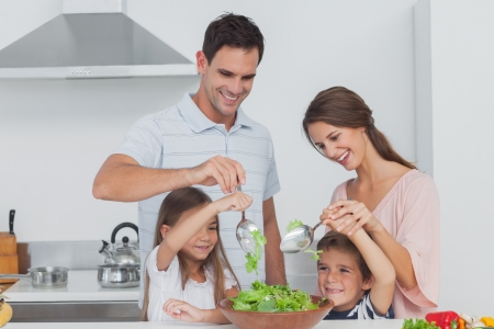 Family mixing a salad together in the kitchen photo