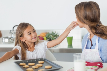 Young girl giving a cookie to her mother in the kitchen photo