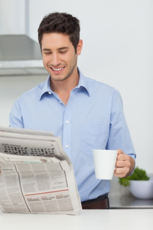 well read: Man with a cup of coffee reading a newspaper in the kitchen Stock Photo