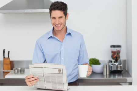 well read: Handsome man reading a newspaper and holding a cup of coffee Stock Photo