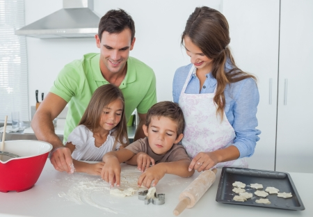 Siblings home baking together in the kitchen with parents photo