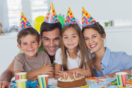 house party: Beautiful family celebrating a party with a chocolate birthday cake Stock Photo