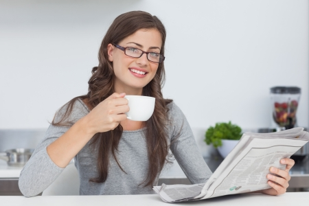 Pretty woman holding a cup of coffee while reading a newspaper photo