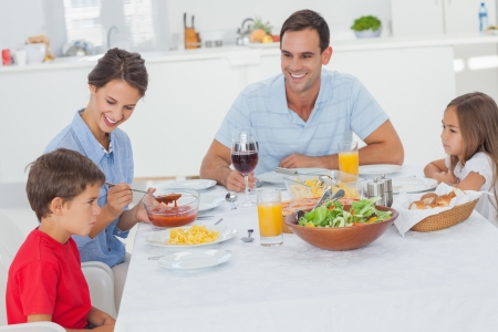 Family eating pasta and salad in the dining room Stock Photo - 20637540