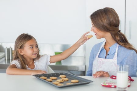 Little girl giving a cookie to her mother in the kitchen photo