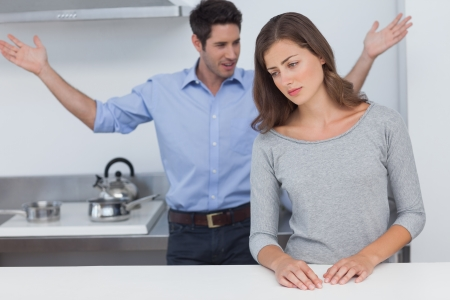 Man gesturing to wife during a dispute in the kitchen photo