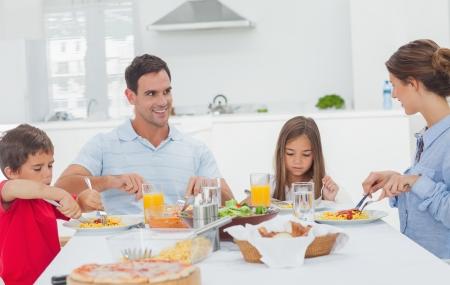 familia comiendo: Familia de comer pasta con salsa para la cena