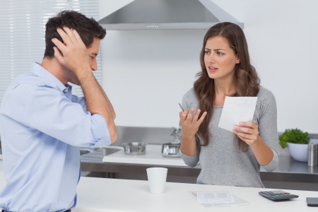 Angry couple doing their accounts in the kitchen photo
