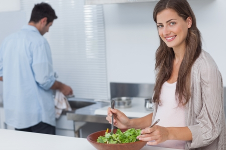Woman mixing a salad in the kitchen while her husband is washing the dishes behind photo