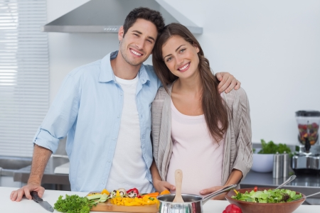 Portrait of a man and his pregnant partner standing in the kitchen photo