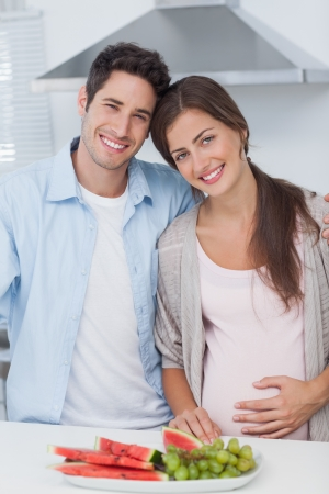 Pregnant woman and her husband standing together in the kitchen photo