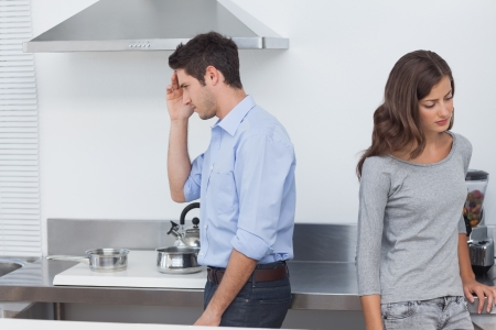 Couple sulking at each other in the kitchen after a dispute photo
