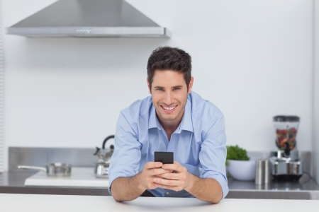 Handsome man typing on his smartphone in kitchen photo