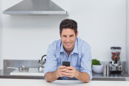 dialing: Hombre guapo escribiendo en su tel�fono inteligente en la cocina Foto de archivo