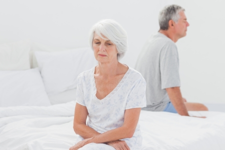 Upset woman arguing with husband on bed  photo