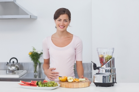 Pregnant woman making a fruit cocktail in the kitchen photo