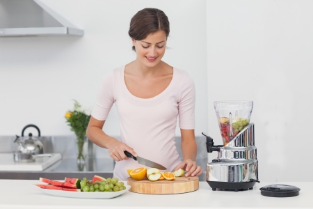 Pregnant woman cutting fruits in the kitchen to make a fruit cocktail photo