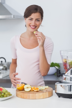 Pregnant woman eating a grape while preparing a fruit cocktail photo