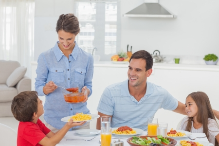 Woman giving pasta sauce to her son for the dinner Stock Photo - 20668346