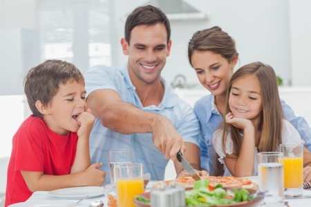 multiracial family: Man cutting a pizza for his family for the dinner Stock Photo