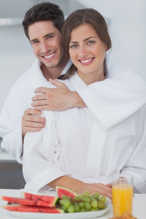 Man embracing his wife who is wearing a dressing gown in the kitchen photo