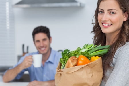 Woman with groceries bag and with her husband holding a cup of coffee on the background photo