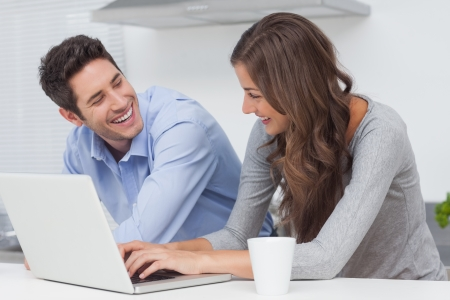 woman typing: Beautiful couple using a laptop in the kitchen Stock Photo