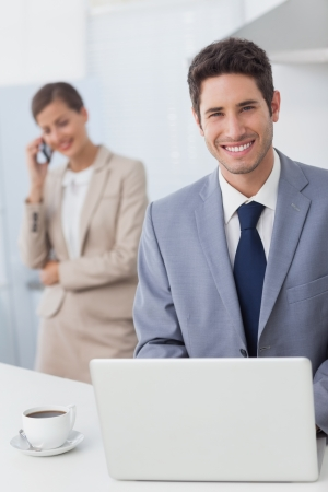 Happy businessman using a laptop before going to work while his wife is on the phone on the background photo