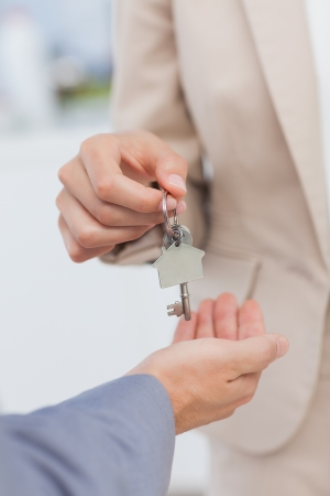 dangling: Estate agent giving house key to a client Stock Photo
