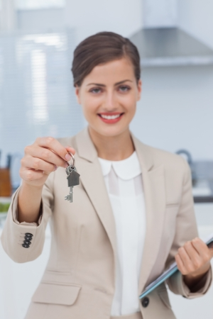 Real estate agent offering house key in a new house photo