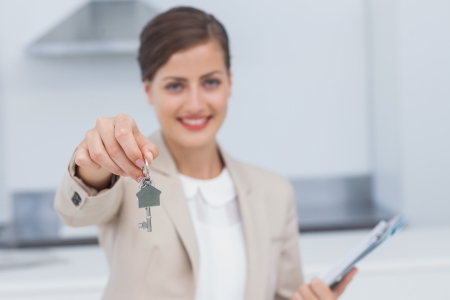 Pretty real estate agent giving house key in a kitchen photo