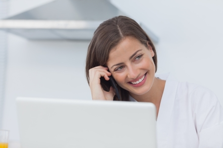 Cheerful woman on the phone using her laptop at the same time photo
