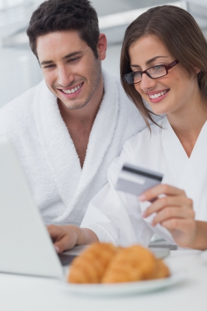 Beautiful couple purchasing online while having breakfast photo
