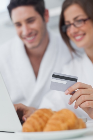 Cheerful couple purchasing online while having breakfast photo