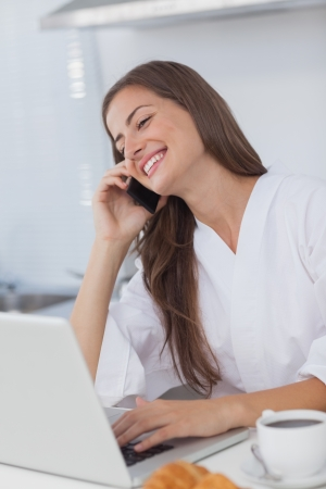 Woman using her laptop while she is phoning at the same time photo