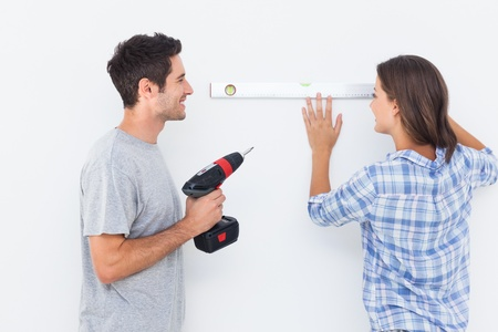 spirit level: Man and his wife doing diy together with a drill and a spirit level Stock Photo