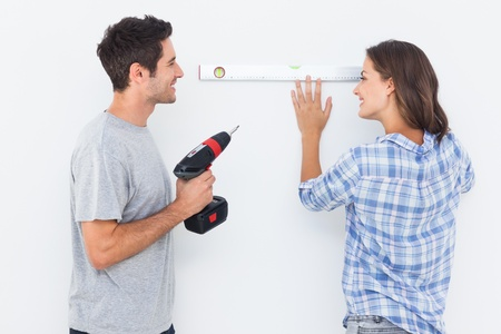 spirit level: Cheerful man and his wife doing home improvements with a drill and a spirit level