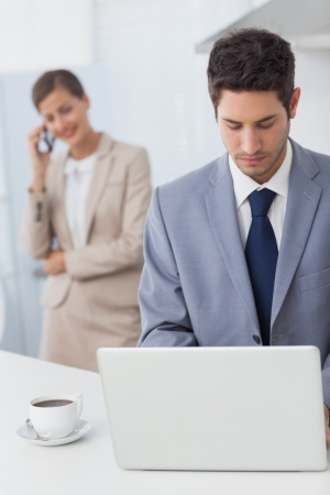 Businessman using a laptop before going to work while his wife is on the phone on the background photo