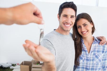 행복한 사람이 자기 부인의 옆에 집 열쇠를 주어지고