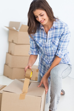 Woman wrapping a box while she is moving home photo