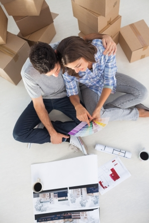 Overview Of A Man And His Wife Looking At House Plans In Their