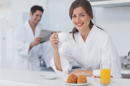 Woman with a dressing gown having breakfast while her husband is reading a newspaper on the background photo