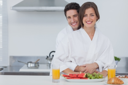 Portrait of a man embracing his wife in the kitchen while having breakfast photo