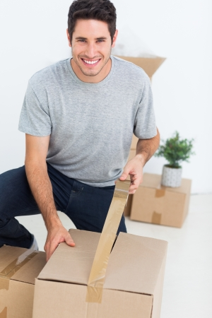 Cheerful man wrapping a box while he is moving home photo
