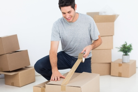Happy man wrapping a box while he is moving home Stock Photo - 20624821