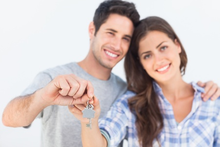 mortgages: Cheerful man and wife holding a key with a house keychain